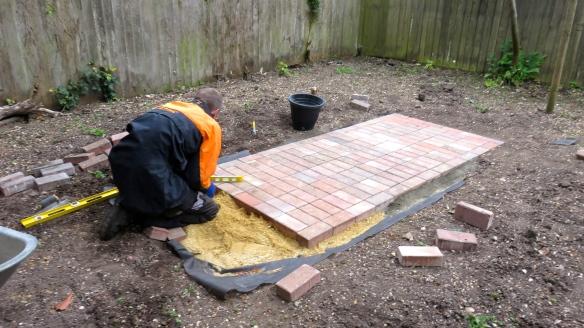 Aaron laying brick paths