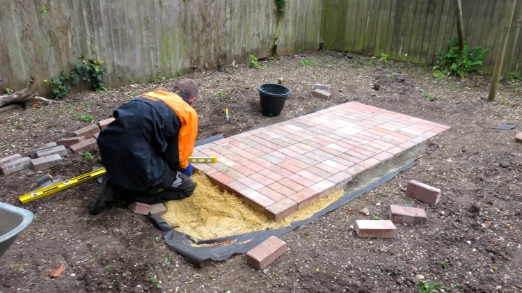 Aaron laying brick paths