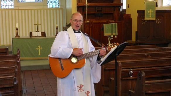 Rev David Farey playing guitar
