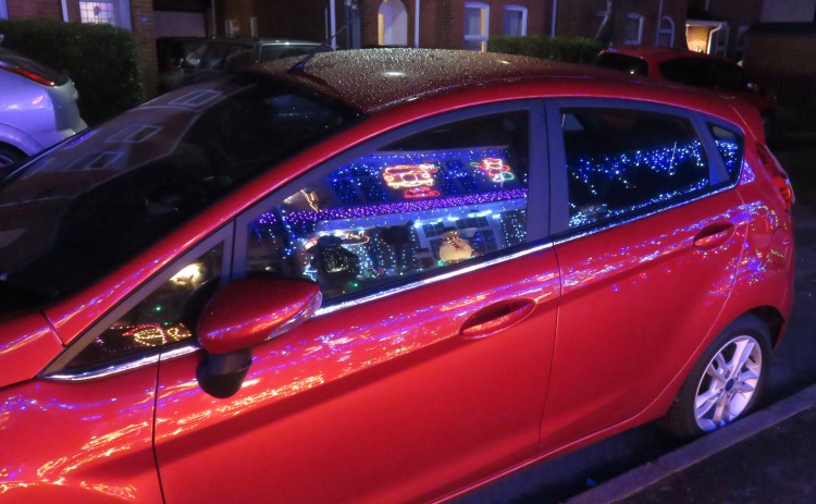 Christmas lights reflected in car