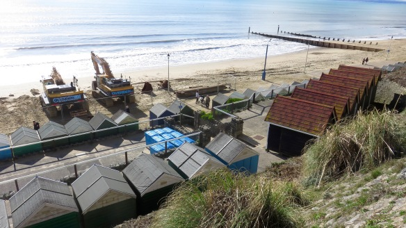 Walkers between diggers and beach huts