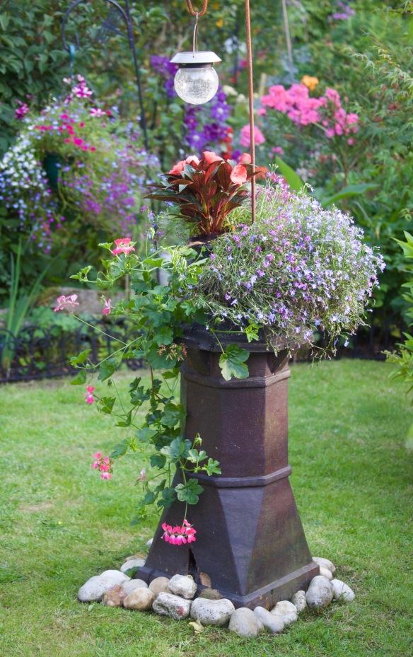 New Guinea impatiens, lobelia, geraniums in chimney pot