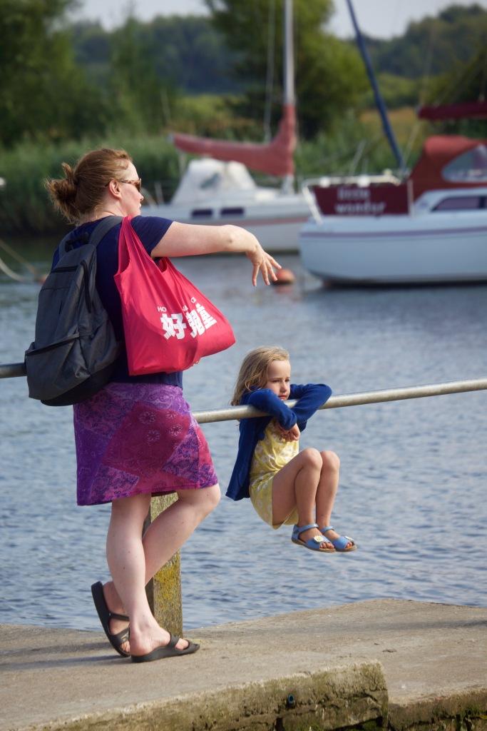 Little girl swinging on rail