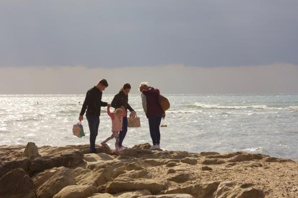 Family on stone breakwater