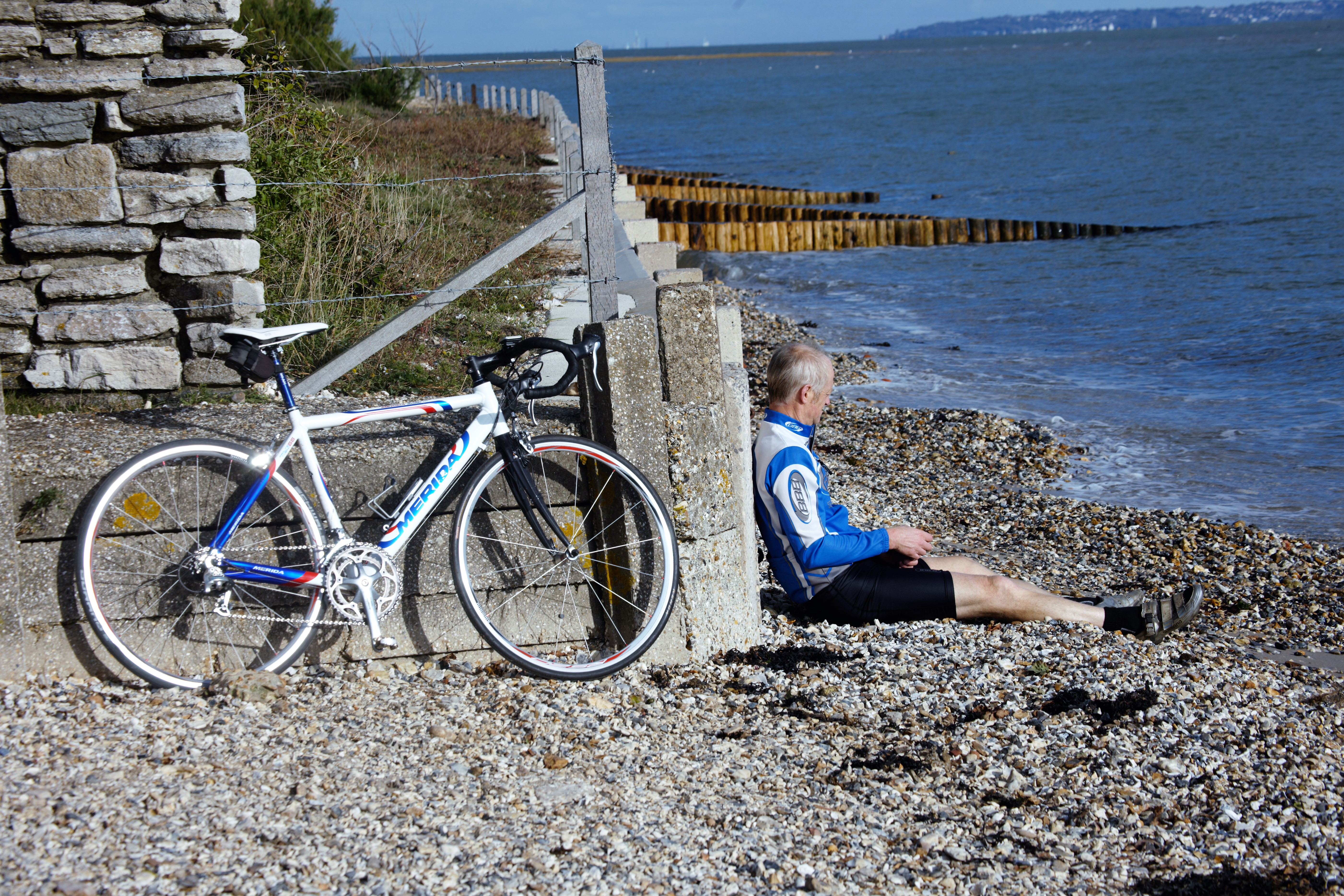 Cyclist resting on shingle