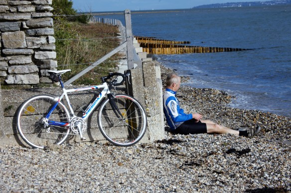 Cyclist resting on shingle