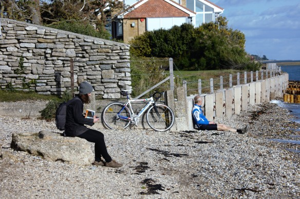 Cyclist and walker resting on shingle