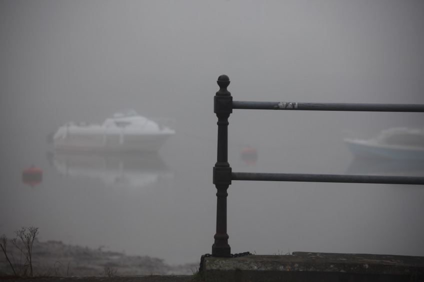 Railing and boats in fog