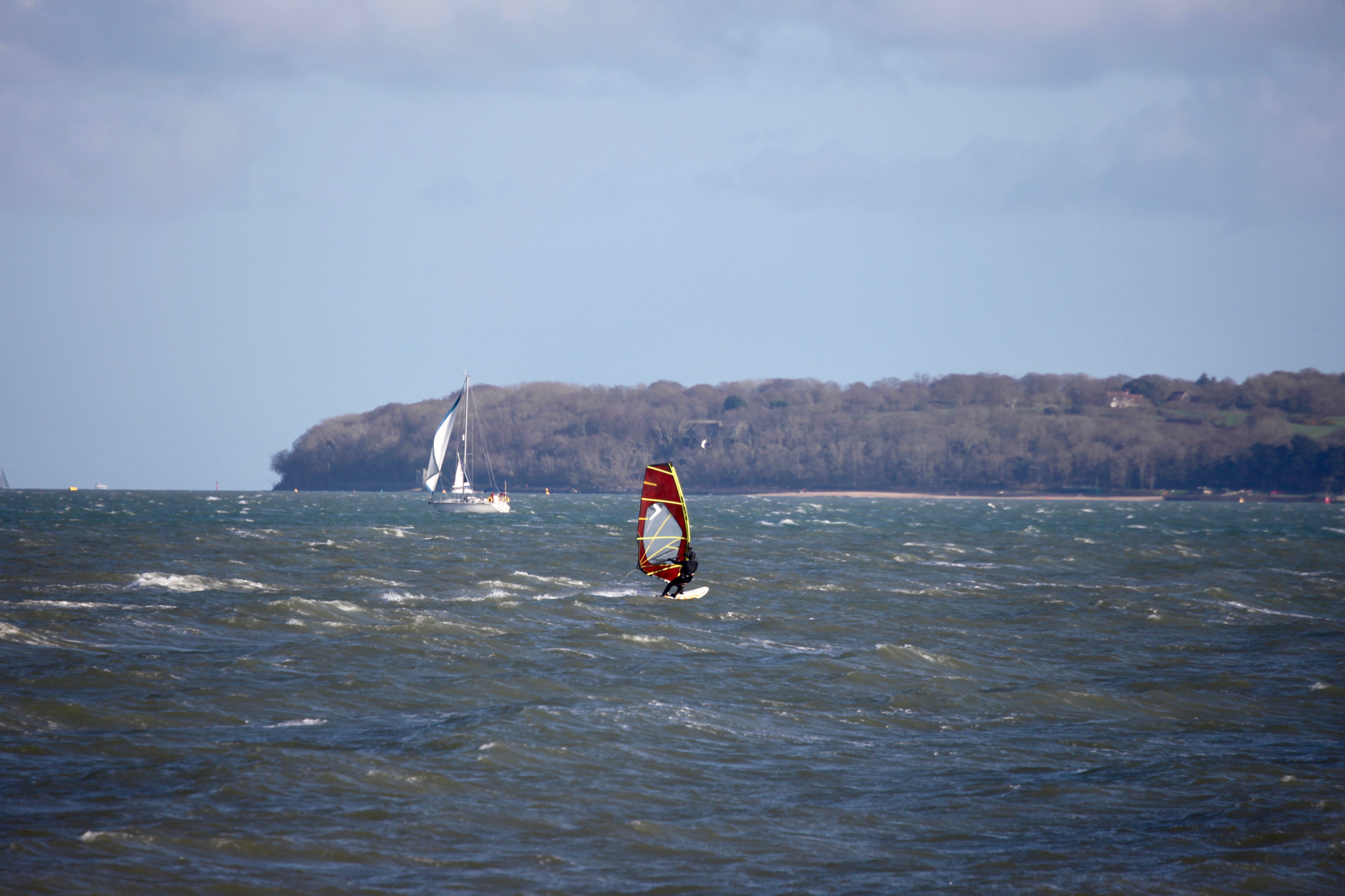 Sailboarder, yacht and Isle of Wight