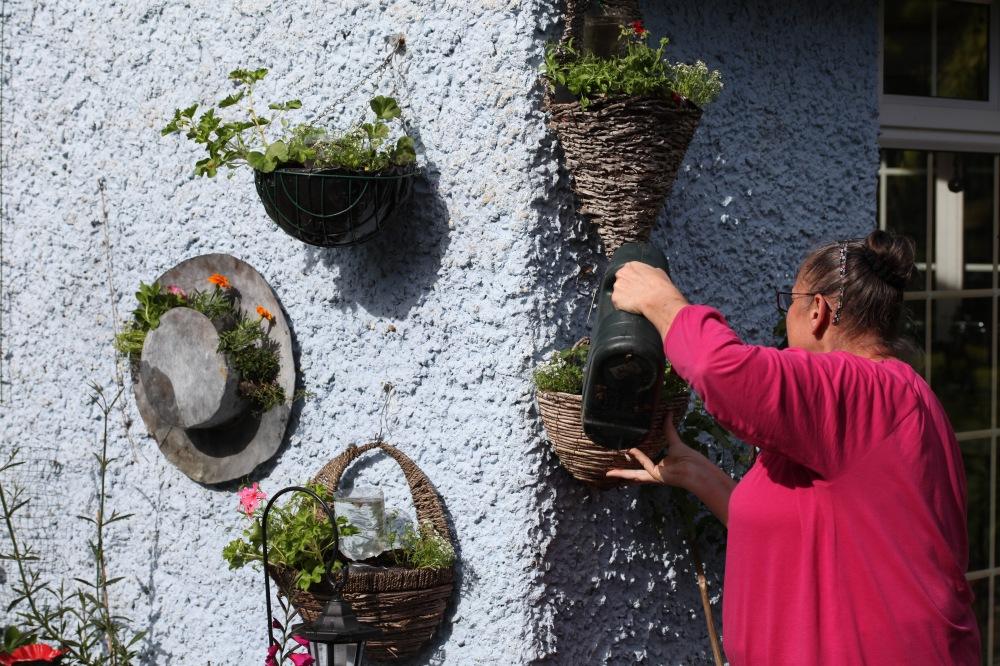 Jackie watering hanging baskets