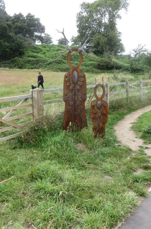 Stag-headed sculptures and dog walker