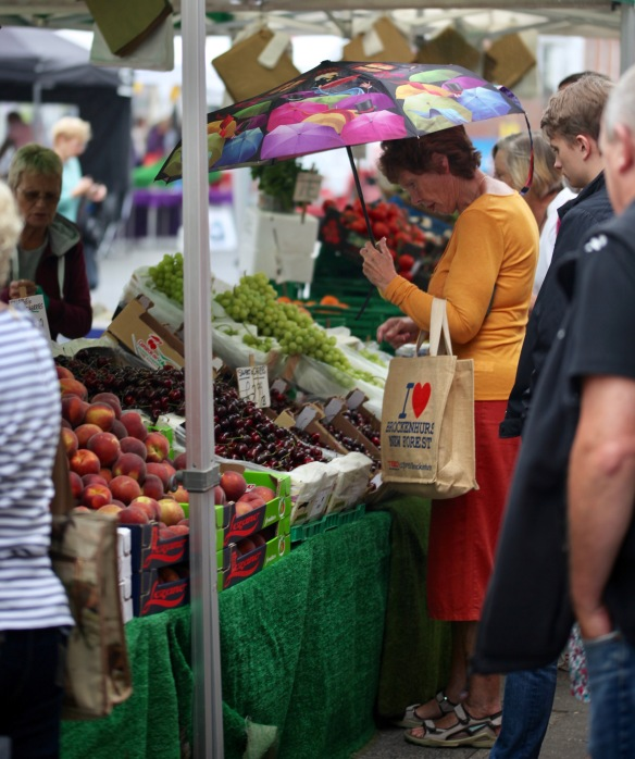 Woman with umbrella at fruit stall