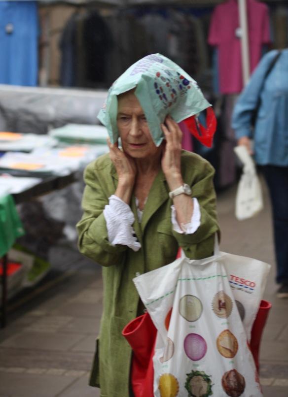 Woman keeping rain off with plastic bag