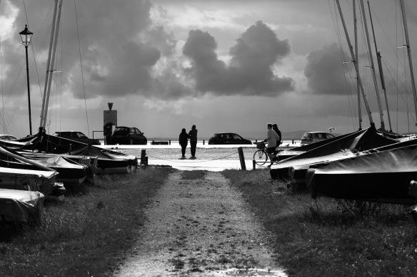 Backlit figures on quay
