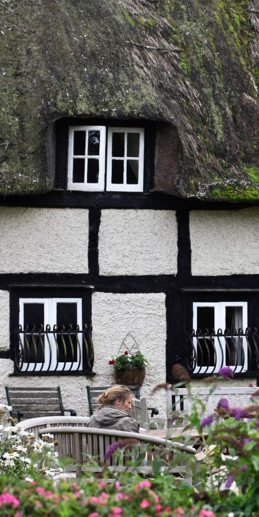 Woman and dog conversing in front of thatched house