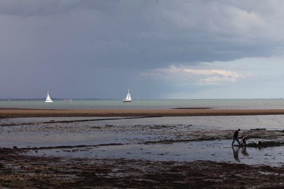 Yachts in sunshine against dark clouds
