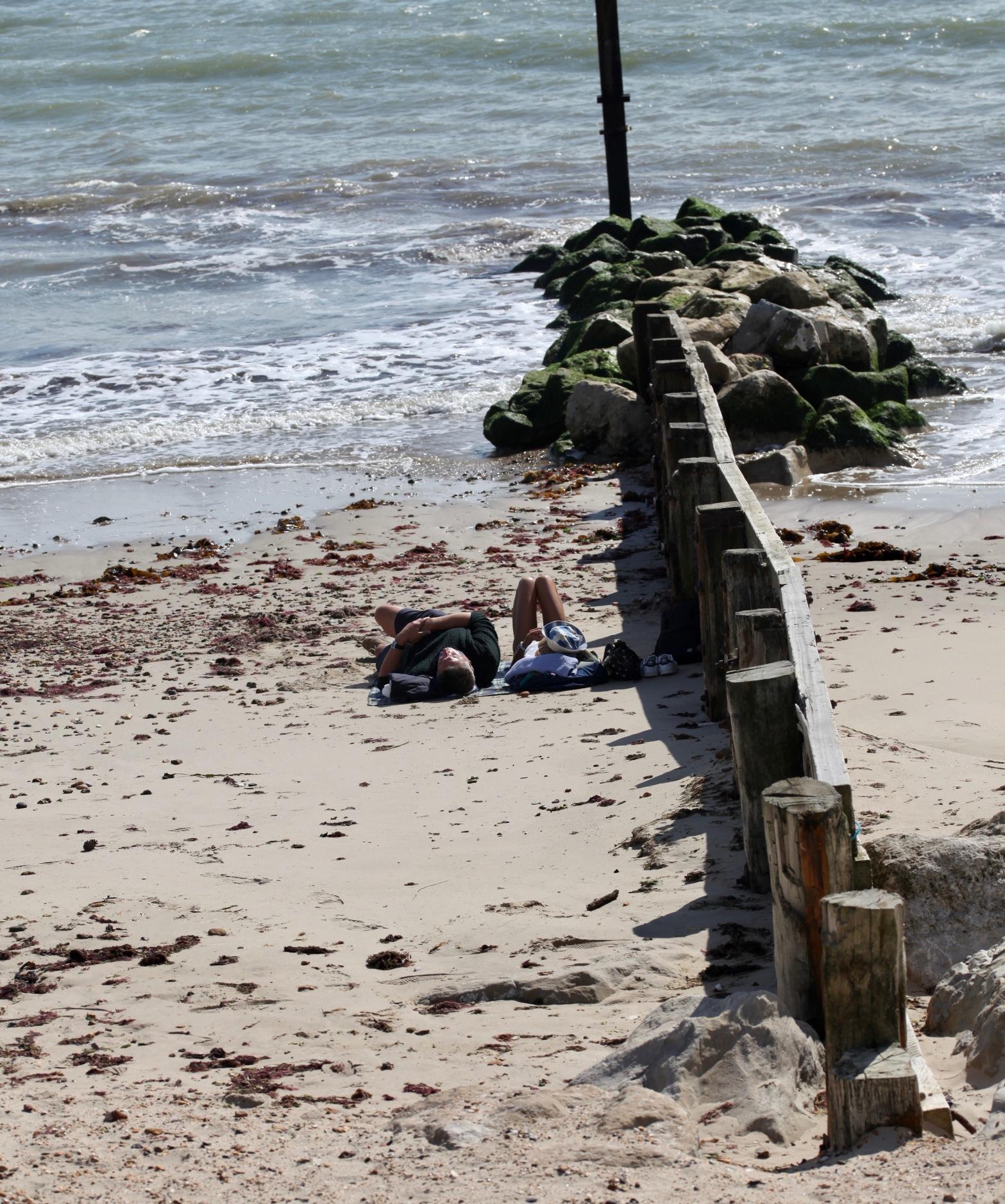Couple on beach beside breakwater