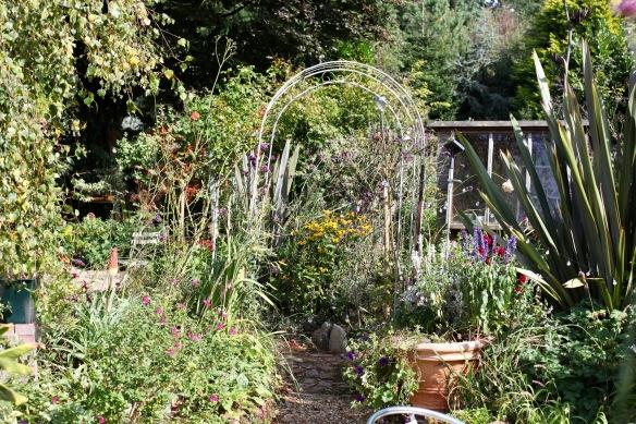 Garden view through arch towards Oval Bed