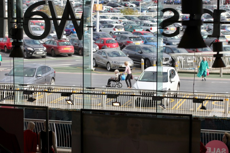 Shoppers through Evans window 1