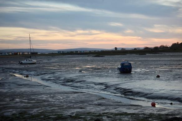 Low tide, boats, beach huts