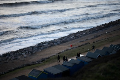 Dog walkers, waves, beach huts