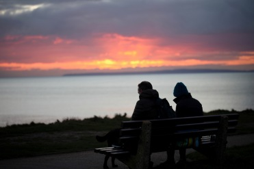 Silhouettes on bench at sunset