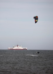 Wind surfer in air and Red Funnel ferry boat