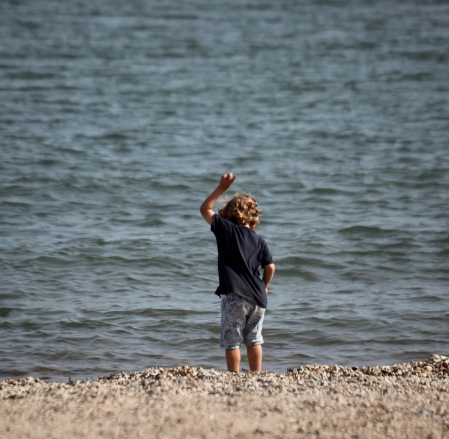 Boy throwing stone into water