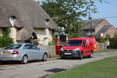 Post van outside thatched cottage