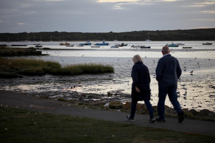 Couple walking past harbour