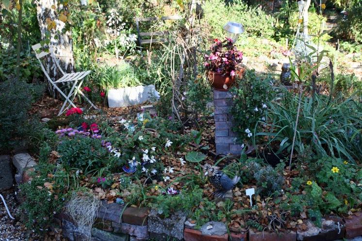 Weeping Birch Bed, asters, begonias, geraniums, petunias, cyclamen, erigeron, carpet rose, owls
